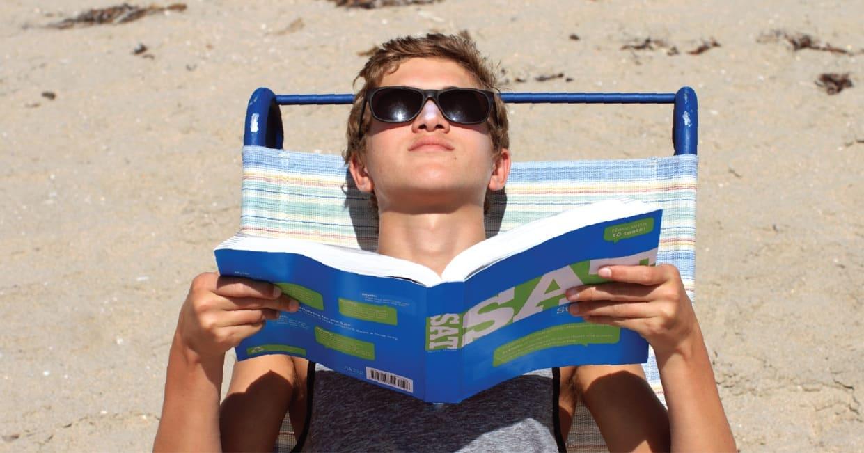 High school boy on beach reading SAT book